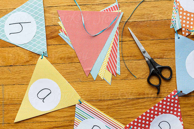 making a paper 'happy birthday' banner by Amanda Large for Stocksy United