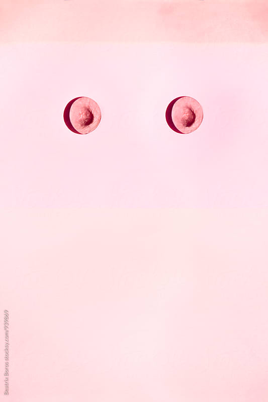 Think pink conceptual photo of two nipples behind a pink surface  by Beatrix Boros for Stocksy United