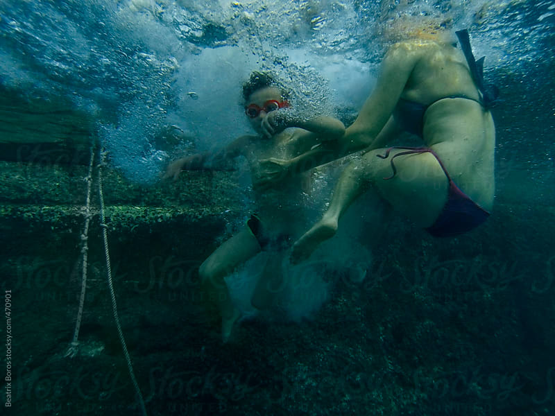 Mother helping her son underwater after his jump by Beatrix Boros for Stocksy United