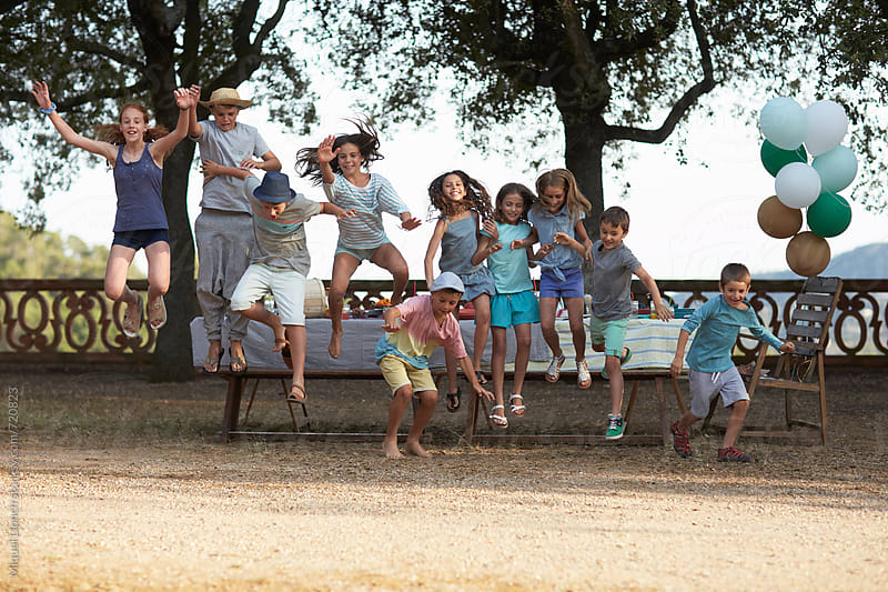 Children jumping and playing at an outdoors party by Miquel Llonch for Stocksy United