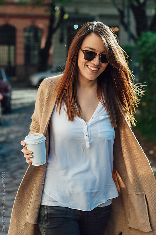 Beautiful young woman with coffee walking down the street by Dimitrije Tanaskovic for Stocksy United