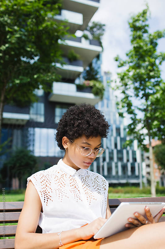 Black young woman using digital tablet outdoors by michela ravasio for Stocksy United
