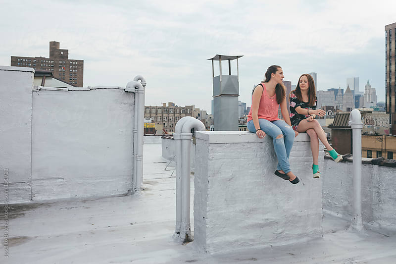 Two Women Smoking Cigarette on a Rooftop in New York by Joselito Briones for Stocksy United