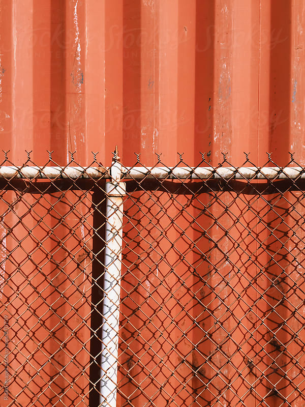 Chain-link fence and metal cargo container by Paul Edmondson for Stocksy United
