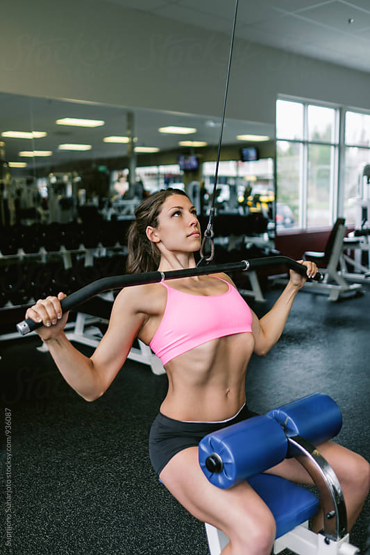Woman working out doing lat pulldown in the gym  by Suprijono Suharjoto for Stocksy United