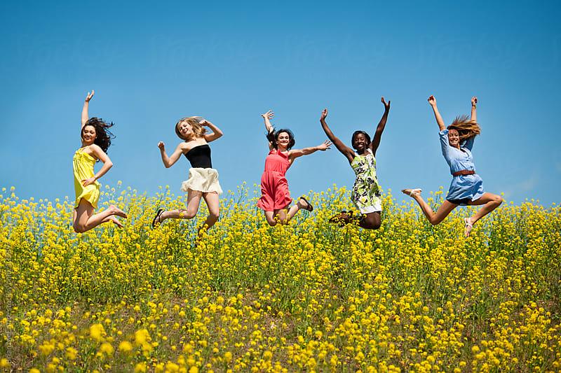High School Senior Girls Jump in Flower Field by Brian McEntire for Stocksy United