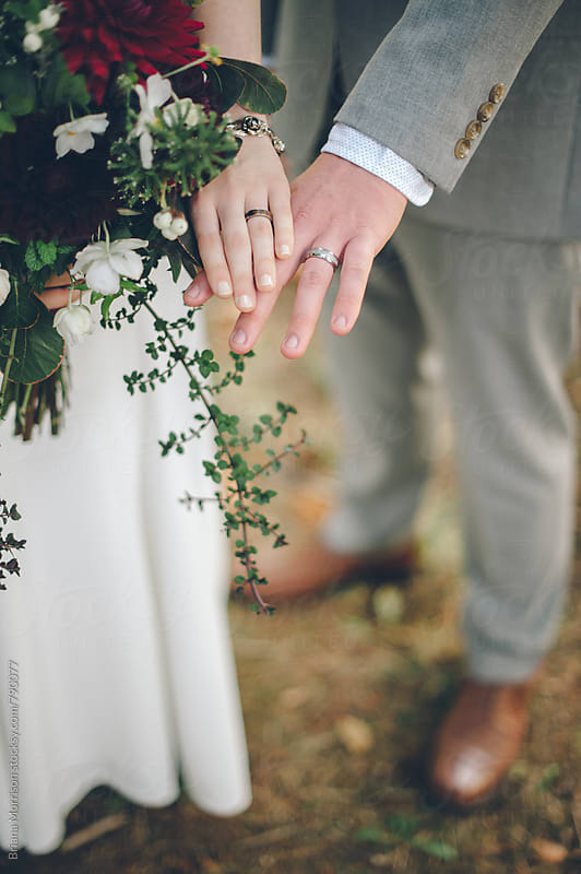 Bride and Grooms Hands with Wedding Rings and Autumn Bouquet by Briana Morrison for Stocksy United