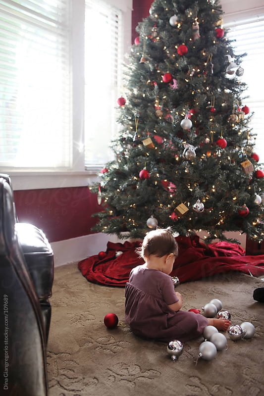 Toddler surrounded by Holiday ornaments  that need to go on Christmas tree nearby by Dina Giangregorio for Stocksy United