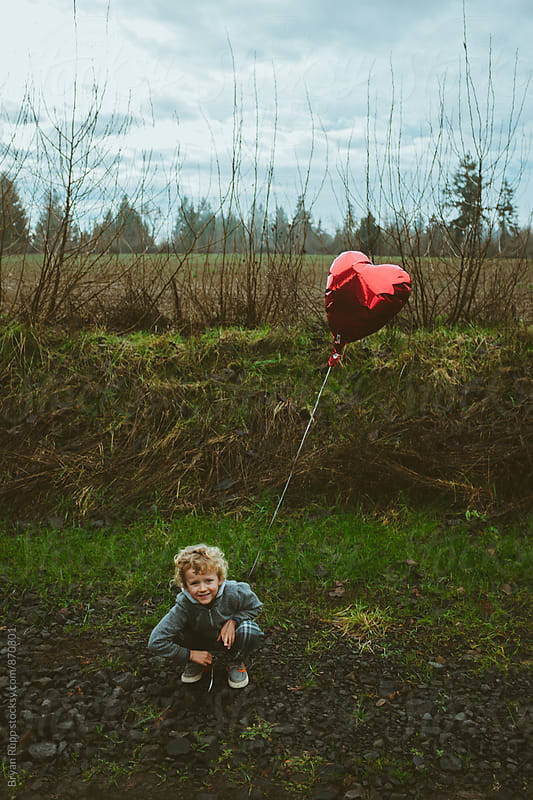 Smiling Little Boy Holding Heart Balloon by Bryan Rupp for Stocksy United