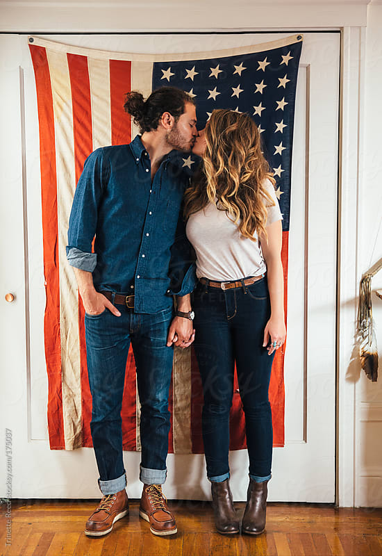 Hipster couple standing in front of American Flag by Trinette Reed for Stocksy United