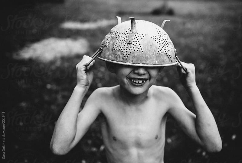 Boy plays outside in his backyard wearing a colander as a hat by Cara Dolan for Stocksy United
