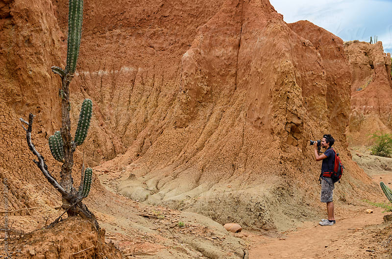 Photographer taking pictures in bright orange canyon with cactus in Tatacoa desert by Alice Nerr for Stocksy United