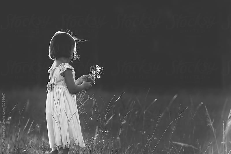 Girl Picks Flowers In A Grassy Field by Alison Winterroth for Stocksy United