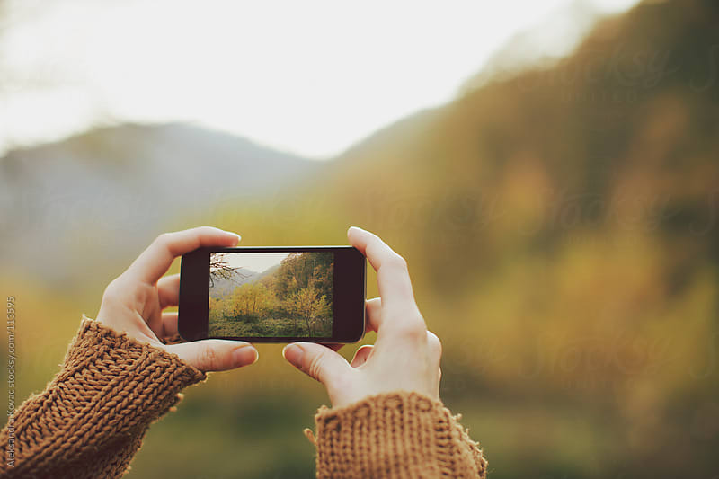 Hands holding phone and taking picture in nature by Aleksandra Kovac for Stocksy United