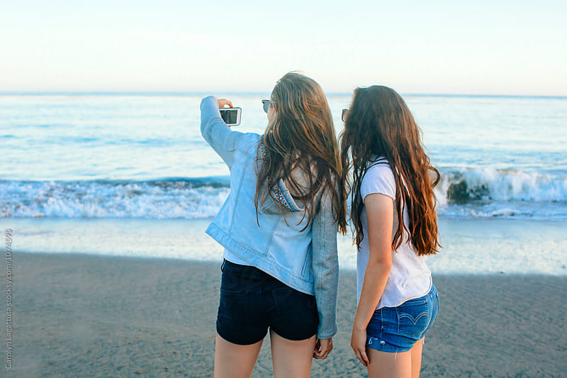 Teenage girls taking a selfie at the beach by Carolyn Lagattuta for Stocksy United