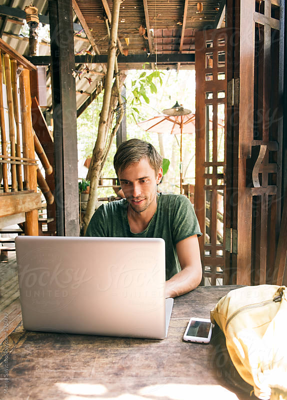 Young Designer Working on Laptop at his Open Space Office by Marija Savic for Stocksy United