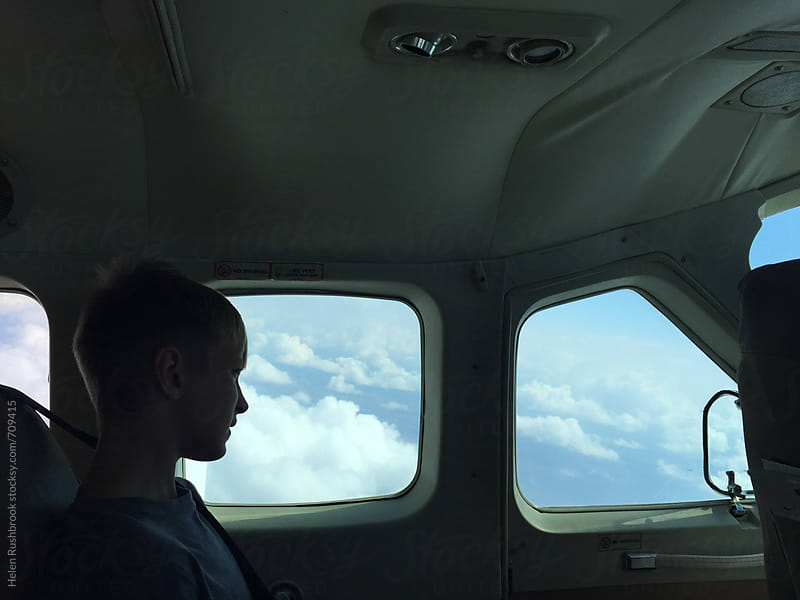 Boy looking out of the window of a light aircraft by Helen Rushbrook for Stocksy United