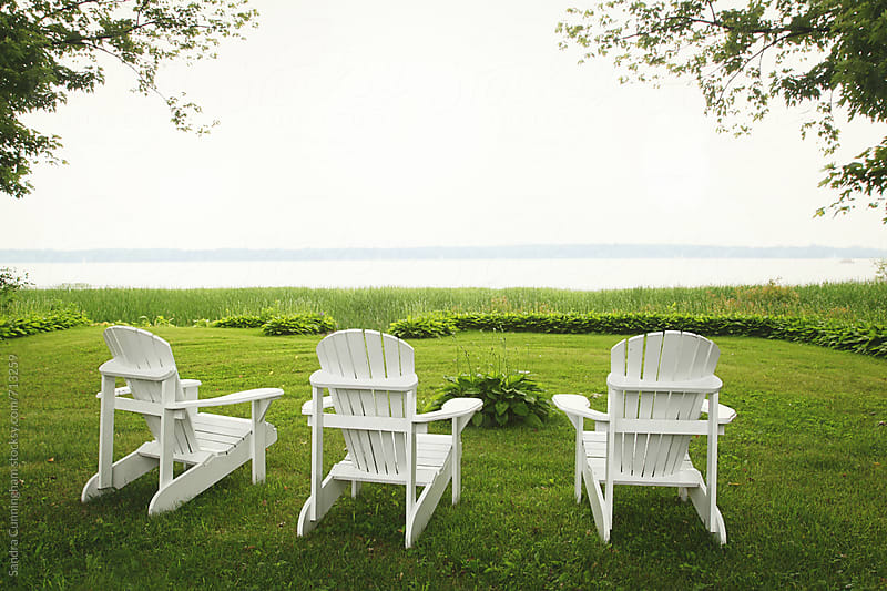 Adirondack chairs by the water by Sandra Cunningham for Stocksy United