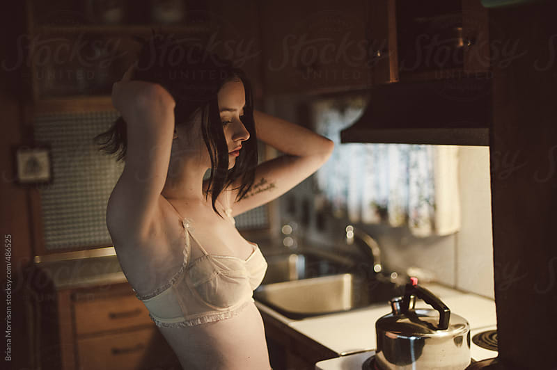 Woman Dressed In A Bra in The Kitchen by Briana Morrison for Stocksy United
