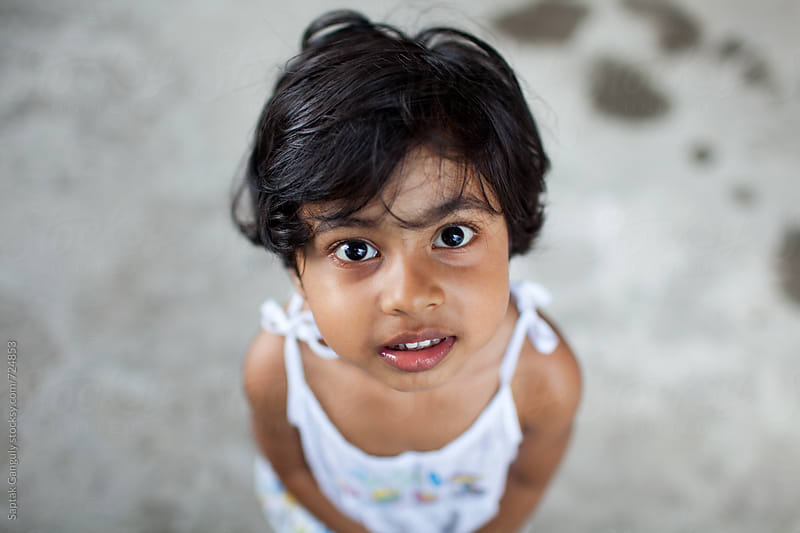 Portrait of cute little girl looking up in amazement by Saptak Ganguly for Stocksy United