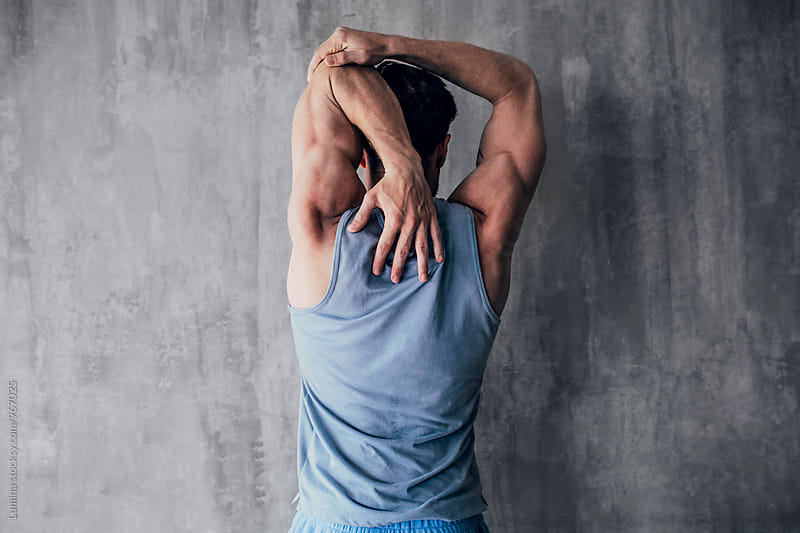 Man Stretching His Hand After a Workout by Lumina for Stocksy United