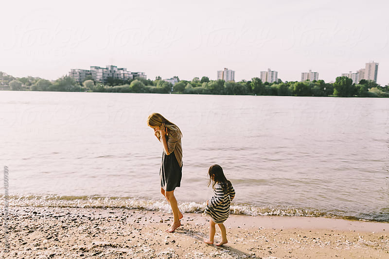 Mother and her little gaughter walking on a sandy river bank by Evgenij Yulkin for Stocksy United