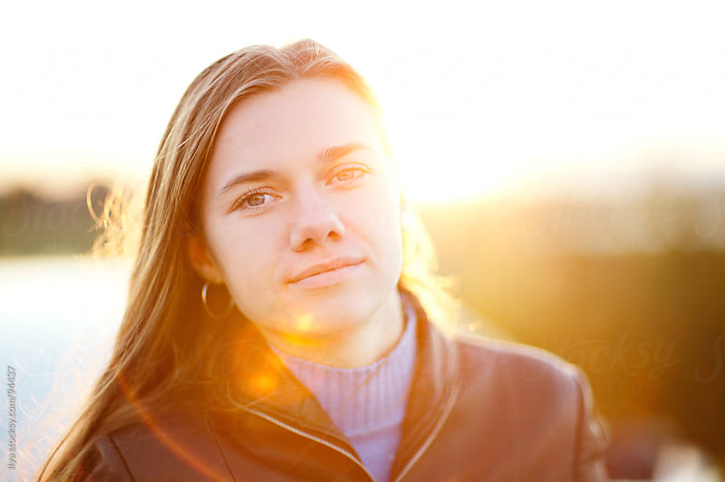 Young woman in sunlight looking at camera by Ilya for Stocksy United