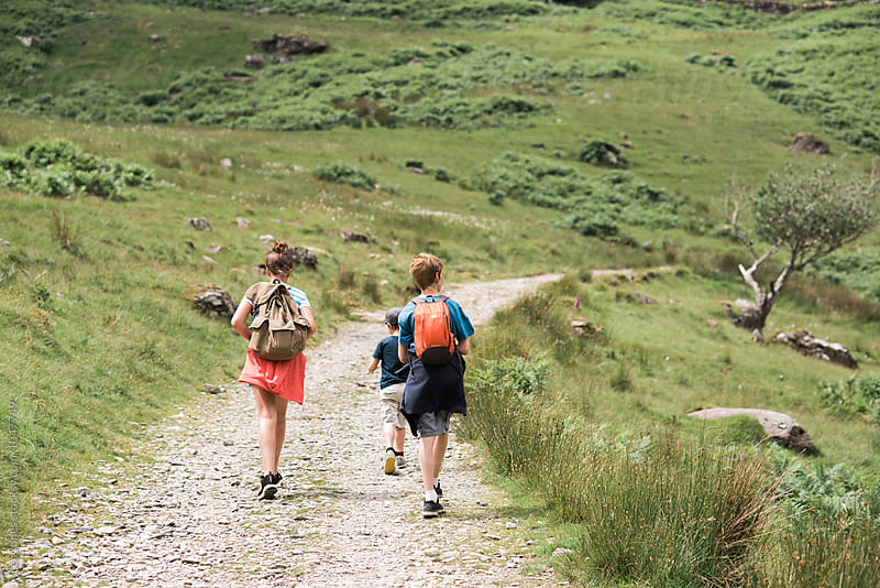 three kids on a walk in the mountains by Léa Jones for Stocksy United