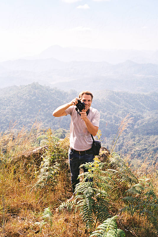 Young man taking pictures on the top of the hill by Dina Lun for Stocksy United
