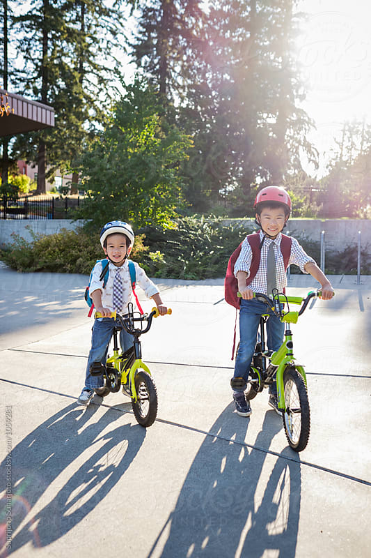 Back to school: Asian kids riding their bicycles in school by Suprijono Suharjoto for Stocksy United