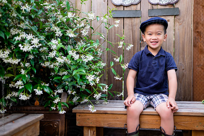 Asian kid sitting on a bench in the backyard by Suprijono Suharjoto for Stocksy United