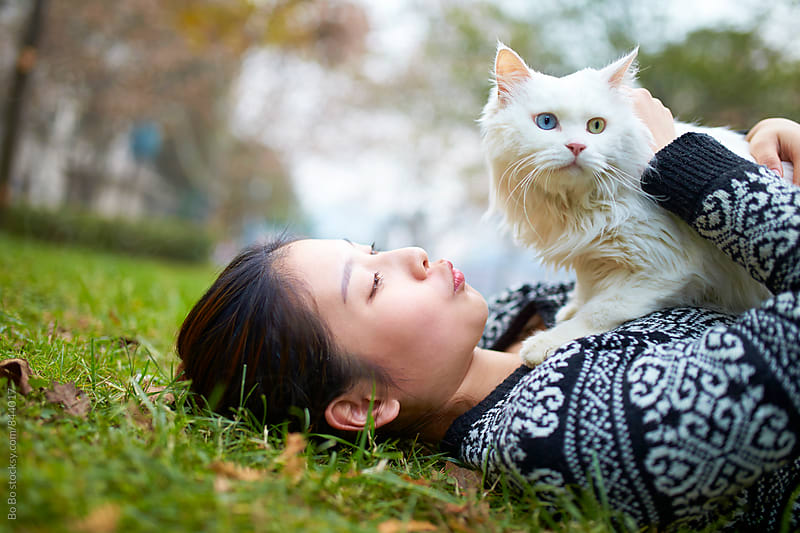 young woman with her cat outdoor by Bo Bo for Stocksy United