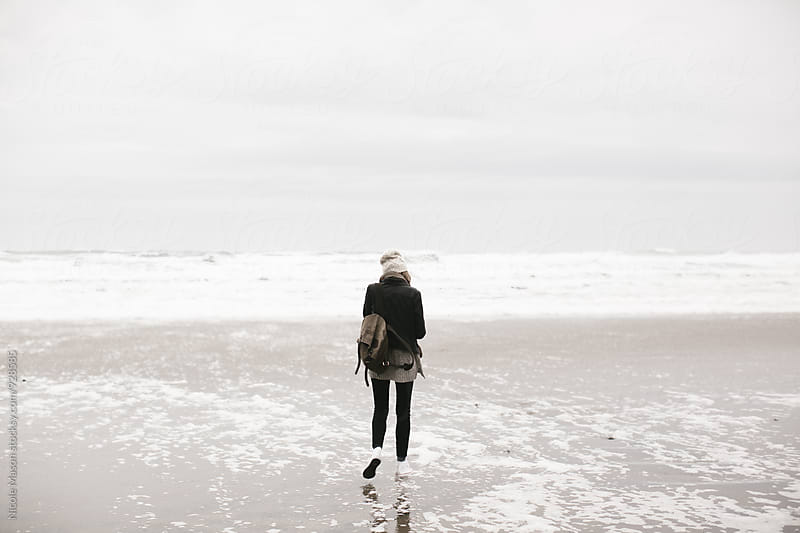young woman walking by ocean on overcast day with camera by Nicole Mason for Stocksy United