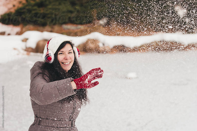 Girl throwing snowballs in the air by Milena Milani for Stocksy United