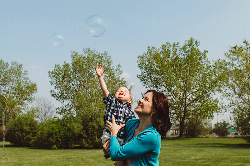 Mother and son catching bubbles by Carey Shaw for Stocksy United