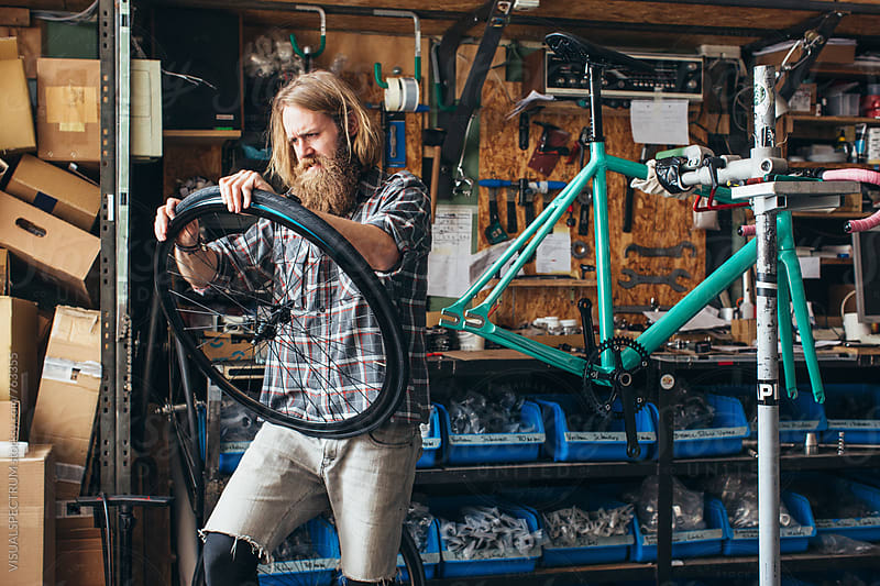 Long-Haired Hipster Mechanic Assembling Tire on Wheel of Fixed Gear Bike in Bright Workshop by VISUALSPECTRUM for Stocksy United
