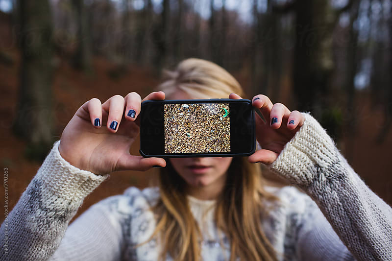 Young woman holding her cell phone with a picture of leaves in front of the face by michela ravasio for Stocksy United