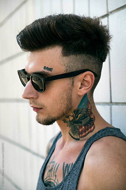 Side view of tattooed man in sunglasses by Danil Nevsky for Stocksy United