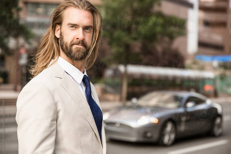 Man standing in front of a sports car by Shaun Robinson for Stocksy United