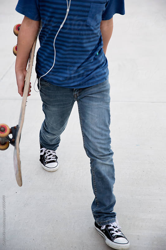 Walking while listening to music and holding his skateboard by Curtis Kim for Stocksy United