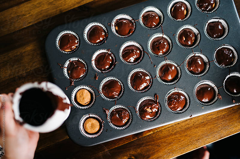 Pouring melted chocolate into Almond butter cups by Cameron Whitman for Stocksy United