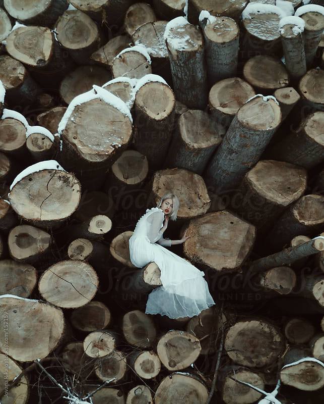Girl sitting on a woodpile by Jovana Rikalo for Stocksy United
