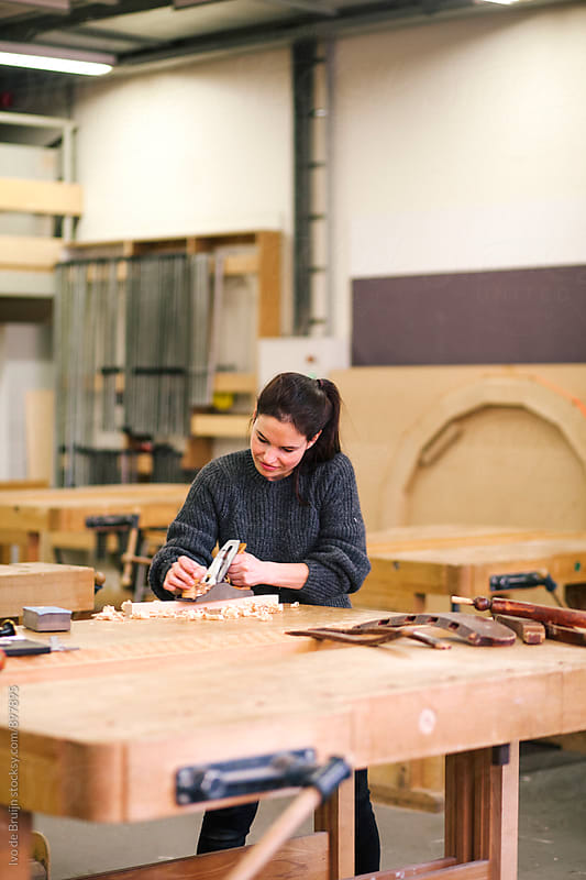 Female woodworker working on a bench with block plane by Ivo de Bruijn for Stocksy United