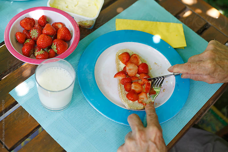 sandwich with strawberries by Rene de Haan for Stocksy United