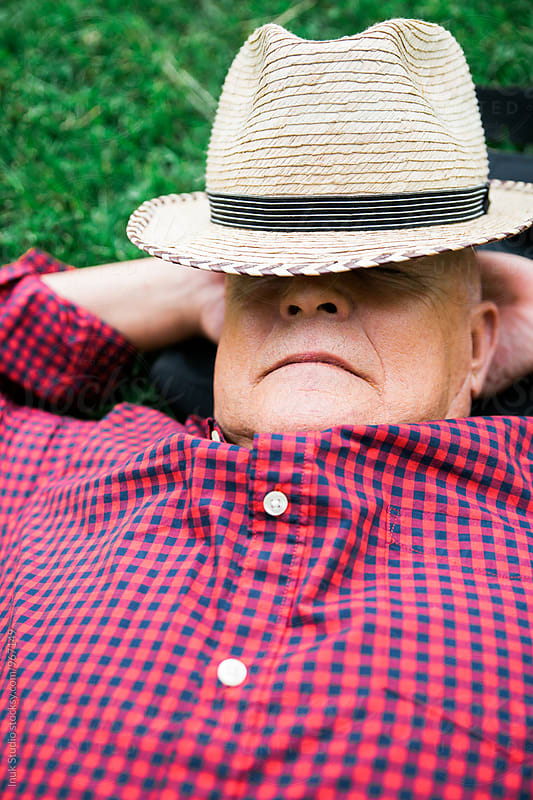 Close-up of sleeping elderly man in park by Inuk Studio for Stocksy United