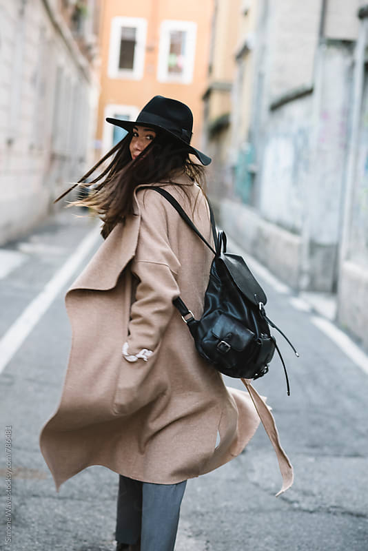 Stylish young woman walking in the city by Simone Becchetti for Stocksy United