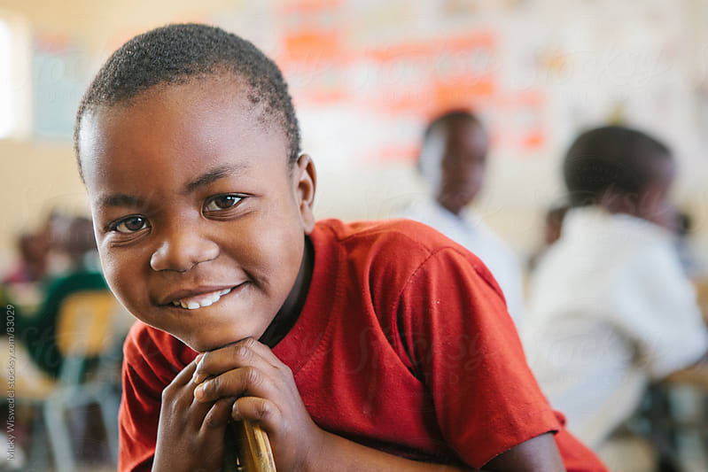 Cute young African Namibian boy in a school classroom by Micky Wiswedel for Stocksy United