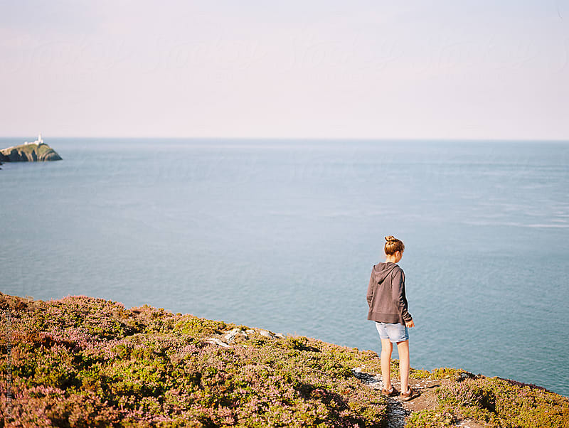 young woman standing by the cliffs by the sea by Léa Jones for Stocksy United