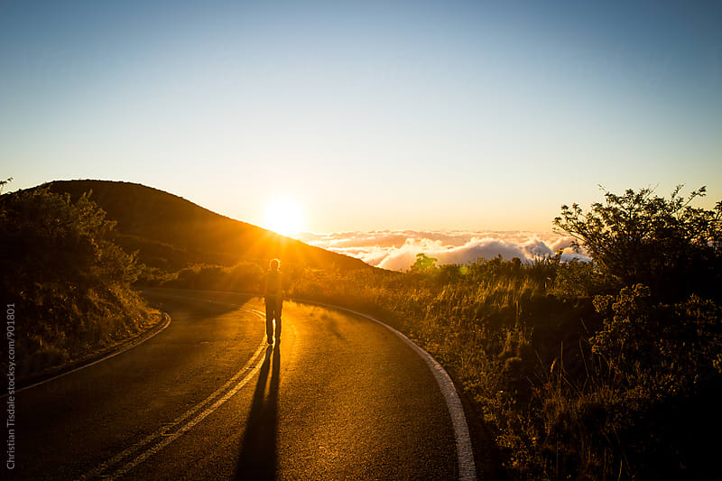 Person walking down road towards sunset on a mountainside by Christian Tisdale for Stocksy United