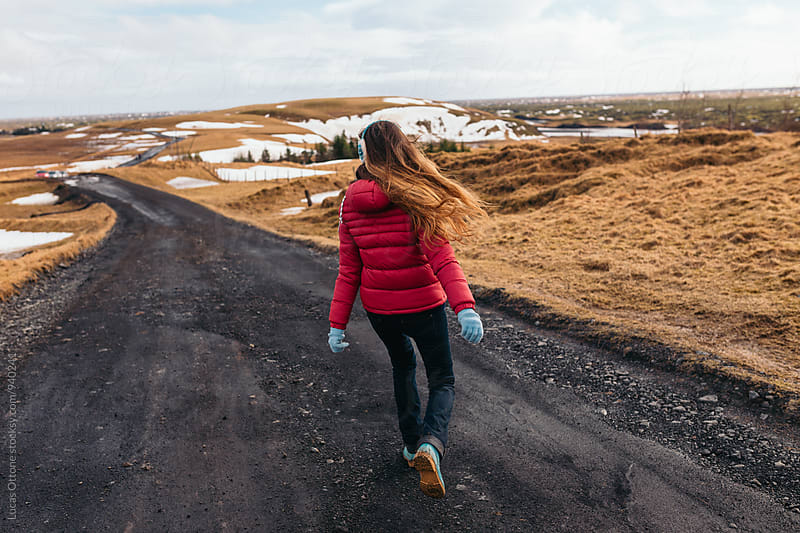Anonymous woman walking down a road in winter by Lucas Ottone for Stocksy United